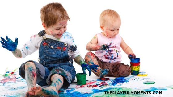 Two kids sitting and playing in paint