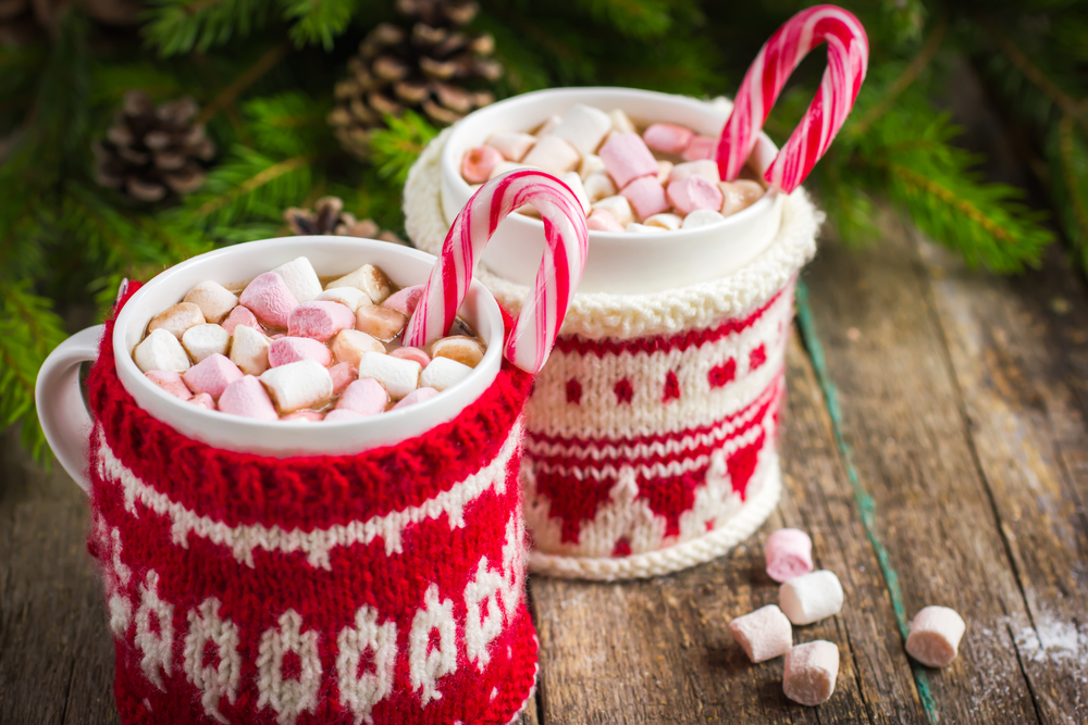 Two red and white mugs of white chocolate with marshmallows and candy canes