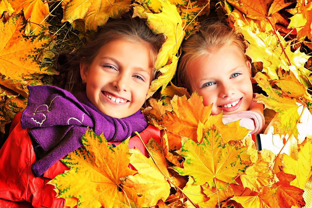 Two-girls-laying-in-fall-maple-leaves-theplayfulmoments