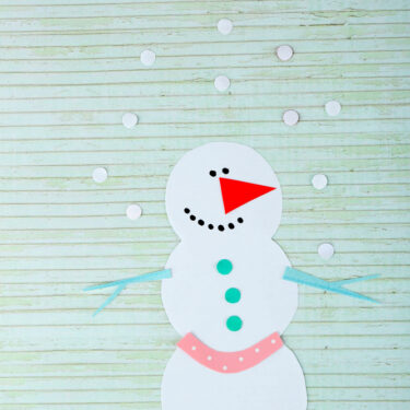 Handmade felt snowman on wooden background